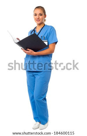 Young female physician reviewing patients records - stock photo
