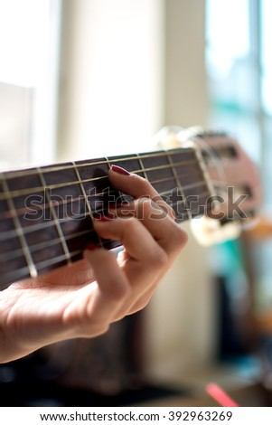 Young female play on the acoustic guitar. - stock photo