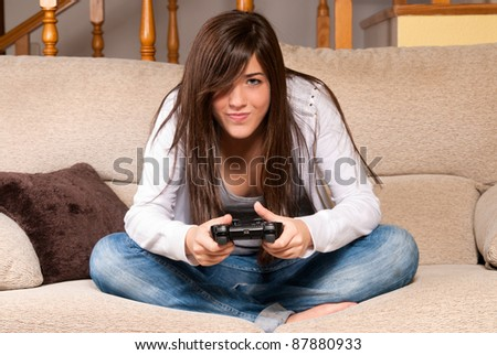 Young female playing video-games concentrating on sofa at home - stock photo