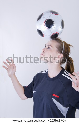 Young female playing with a soccer ball. White background - not isolated. - stock photo