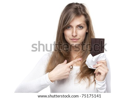 Young female pointing with her finger at the chocolate in bars looking at the camera isolated on white background - stock photo