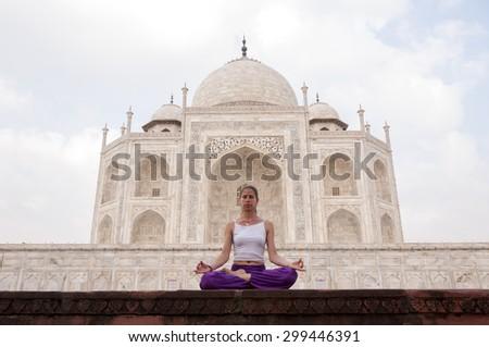 Young female practising yoga meditation at Taj Mahal, India - stock photo
