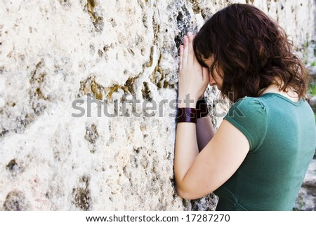 Young female prayer against stone wall. - stock photo