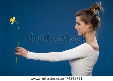 Young female presenting a flower on blue background, side view - stock photo