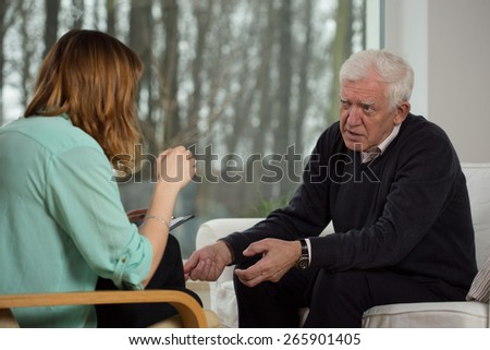 Young female psychologist advising to older man - stock photo
