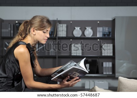 Young female reading a magazine in the living-room - stock photo