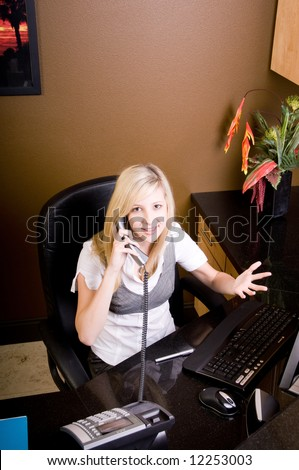 Young female receptionist frustrated on the telephone