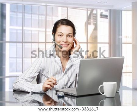 Young female receptionist works on laptop computer in brightly lit office. Daylight, indoor, office. - stock photo