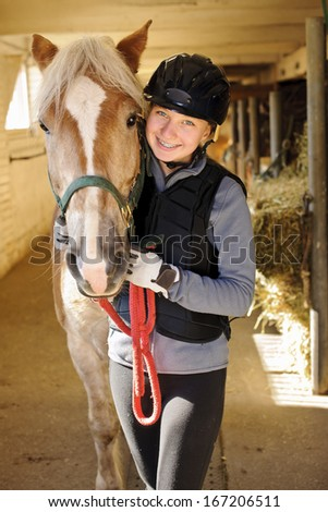 Young female rider with horse inside stable - stock photo