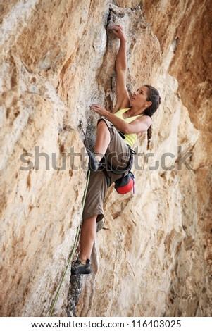 Young female rock climber on a cliff face - stock photo