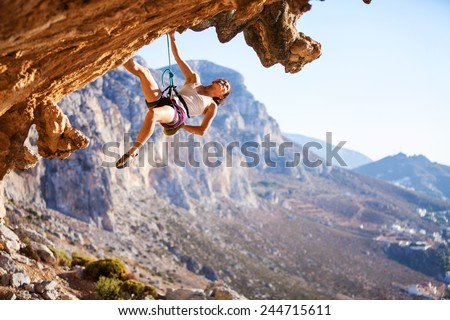 Young female rock climber on overhanging cliff - stock photo