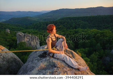 Young female rock climber sitting secured with rope on big rock at mountain peak with bare foot enjoying beautiful sunset view. Warm sunny summer evening in the mountains. Climbing equipment. - stock photo