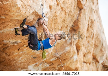 Young female rock climber struggling to make next movement up - stock photo