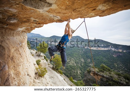 Young female rock climber struggling to make the next movement up - stock photo