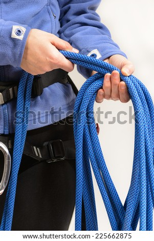 Young female rock climber wearing safety harness rolling blue climbing rope on white background