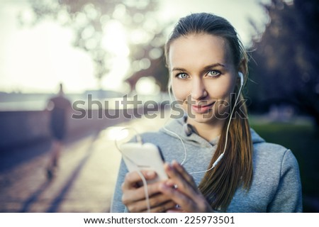 Young female runner is having break and listening to music during the run in city on a quay - stock photo