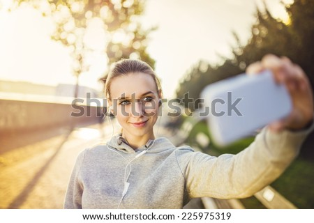 Young female runner is having break and taking selfie during the run in city on a quay - stock photo