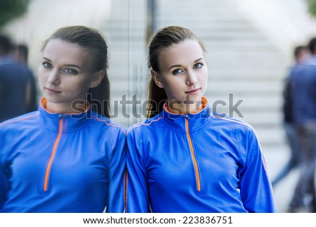 Young female runner is having break during the run in city center - stock photo