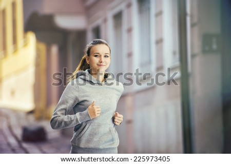Young female runner is jogging on tiled pavement old city on center. Healthy lifestyle. - stock photo