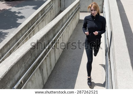 Young female runner is training in city center  - stock photo