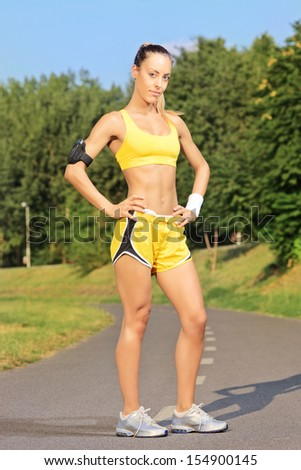 Young female runner posing on a running track in park on a sunny day - stock photo