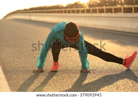 Young female runner stretching her legs on sunrise road - stock photo