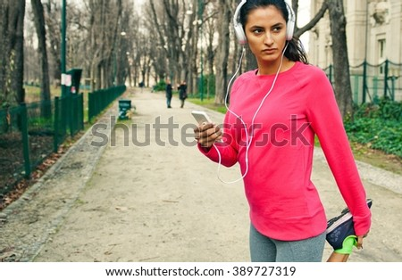 Young female runner using her smart phone after jogging. She is stretching while listening to music - stock photo