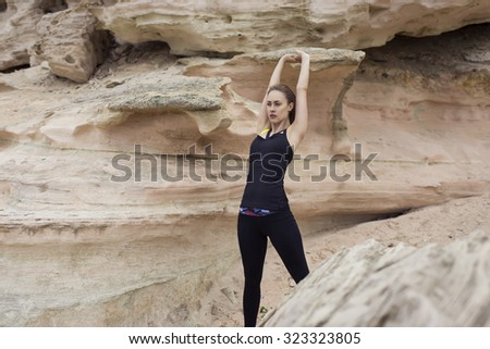 Young female runner warming up before began her daily fitness training outdoors in nature landscape, attractive sportive woman with beautiful figure doing stretching exercise for arms before her jog - stock photo