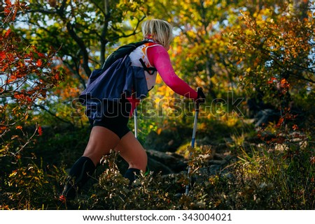 young female runner with nordic walking poles in forest, climbs a mountain trail. autumn landscape, fallen leaves - stock photo