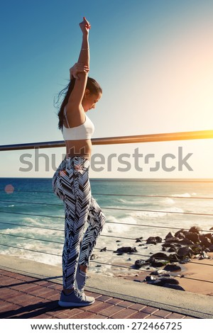 Young female runner with sexy body in sport bra and training tights warming up before workout outdoors, sporty woman stretching arms while standing on wooden pier with ocean waves on background, flare - stock photo