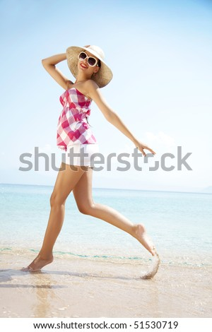 young female running on the beach - stock photo