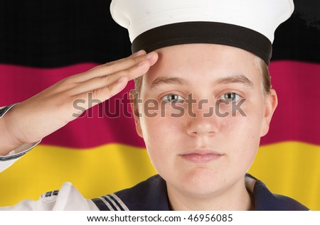 young female sailor saluting in front of german flag - stock photo
