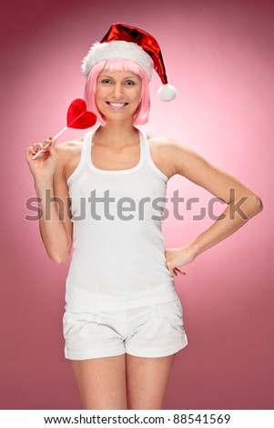 Young female santa in flaunting pink wig with a heart lollypop over red background - stock photo