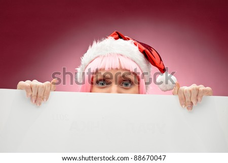 Young female santa in pink wig holding a christmas clear white card over red background - stock photo