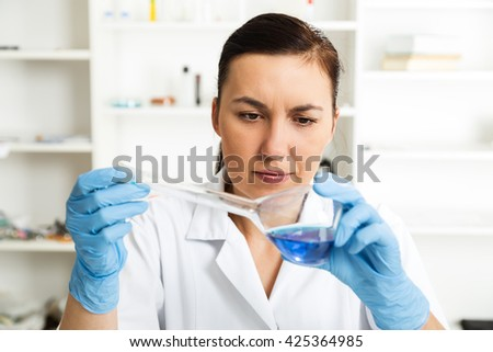 Young Female Scientist Analyzing Sample In Laboratory.laboratory assistant analyzing a sample.