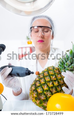 Young female scientist  in laboratory with grinder and pineapple