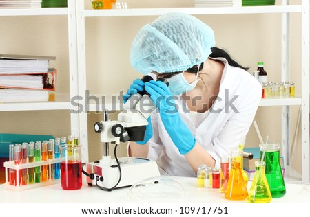 Young female scientist looking at microscope in chemistry laboratory - stock photo