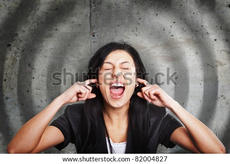 Young female screaming while covering her ears