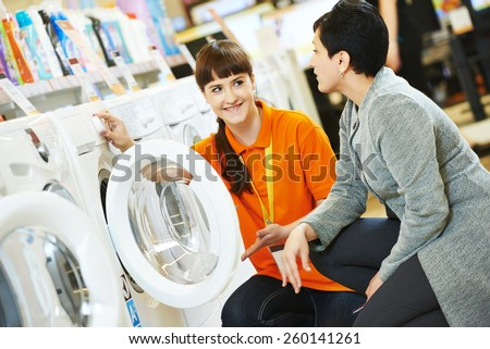 Young female seller assistant helps woman to choose washing machine in home appliance shopping mall supermarket - stock photo