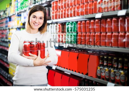 Young female shopper searching for beer pack in supermarket