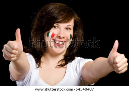 young female show thumb up gesture, italian team supporter with flags painted on her cheeks, studio shoot isolated on black background
