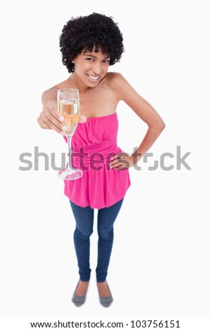 Young female showing a great smile while holding a glass of white wine - stock photo