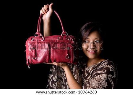 Young female showing off her new red leather handbag.