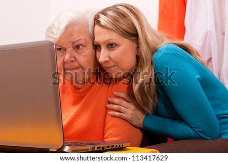 young female shows an senior how to use modern technology