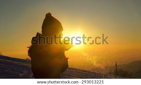 Young female silhouette blowing snow on sunset