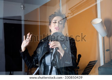 Young female singer seen through glass in recording studio