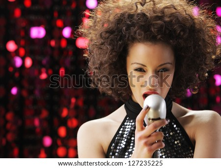Young female singer with brown curly hair singing a song - stock photo