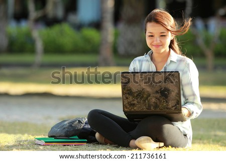 Young female sitting cross-legged on grass with laptop and books doing a homework - stock photo