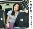 Young female sitting in the trunk of a car with suitcases, showing thumb up sign, ready to leave for vacations - stock photo