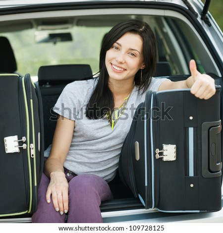 Young female sitting in the trunk of a car with suitcases, showing thumb up sign, ready to leave for vacations